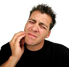 Man holding his jaw in pain in need of some sedation dental care